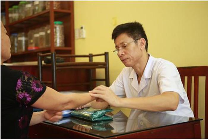 Hình ảnh Ths.Bs Ngô Quang Hùng đang bắt mạch cho bệnh nhân